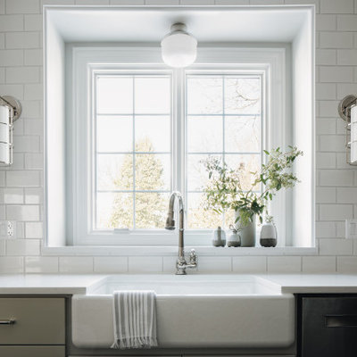 Example of a mid-sized transitional dark wood floor eat-in kitchen design in Chicago with a farmhouse sink, shaker cabinets, gray cabinets, quartz countertops, white backsplash, ceramic backsplash, paneled appliances, an island and white countertops