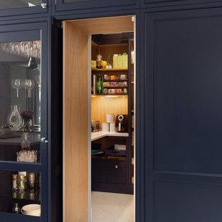 Inredning av ett klassiskt stort vit vitt kök, med en rustik diskho, luckor med profilerade fronter, blå skåp, bänkskiva i kvartsit, stänkskydd med metallisk yta, spegel som stänkskydd, rostfria vitvaror, klinkergolv i keramik, en köksö och blått golv