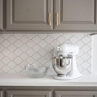 Пример оригинального дизайна: маленькая параллельная кухня в современном стиле с серыми фасадами, белым фартуком, фартуком из керамической плитки, полом из цементной плитки, обеденным столом, фасадами с выступающей филенкой и техникой из нержавеющей стали без острова