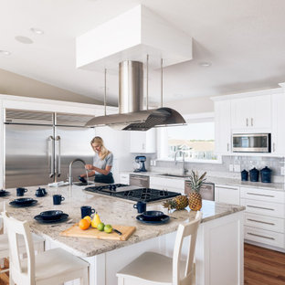 Large coastal kitchen designs - Example of a large beach style l-shaped medium tone wood floor and brown floor kitchen design in Other with an undermount sink, shaker cabinets, white cabinets, granite countertops, gray backsplash, stainless steel appliances, an island, subway tile backsplash and multicolored countertops