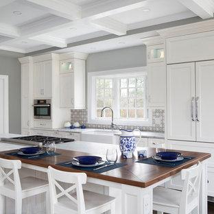 Идея дизайна: кухня в стиле современная классика с раковиной в стиле кантри, плоскими фасадами, белыми фасадами, столешницей из гранита, синим фартуком, фартуком из керамической плитки, черной техникой, темным паркетным полом, двумя и более островами и фиолетовым полом