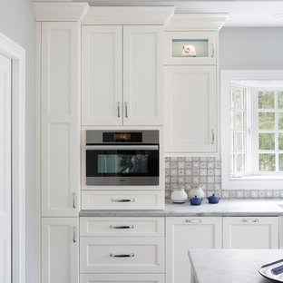 フィラデルフィアのトランジショナルスタイルのおしゃれなマルチアイランドキッチン (エプロンフロントシンク、フラットパネル扉のキャビネット、白いキャビネット、御影石カウンター、青いキッチンパネル、セラミックタイルのキッチンパネル、黒い調理設備、濃色無垢フローリング、紫の床) の写真