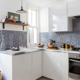 Small eclectic u-shaped separate kitchen in London with a drop-in sink, flat-panel cabinets, white cabinets, black splashback, ceramic splashback, stainless steel appliances, ceramic floors, no island and stainless steel benchtops.