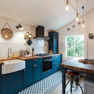 Idée de décoration pour une cuisine parallèle design de taille moyenne avec un évier de ferme, un placard à porte shaker, des portes de placard bleues, un plan de travail en bois, une crédence beige, une crédence en carrelage métro, un électroménager noir, un sol en carrelage de céramique et un îlot central.