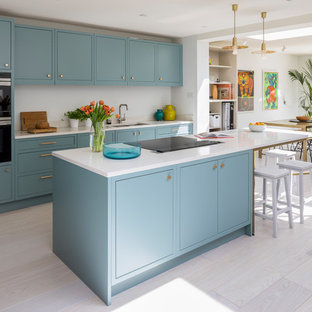 Medium sized contemporary galley open plan kitchen in London with a double-bowl sink, flat-panel cabinets, blue cabinets, quartz worktops, stainless steel appliances, light hardwood flooring, an island, white floors, white worktops and white splashback.