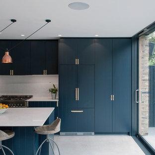 Photo of a medium sized modern galley kitchen/diner in London with an integrated sink, quartz worktops, grey splashback, stone slab splashback, stainless steel appliances, concrete flooring, an island and grey floors.