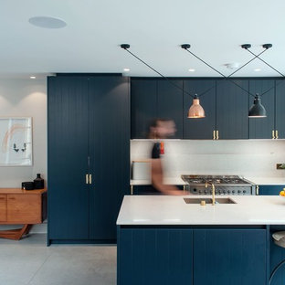 Mid-sized transitional eat-in kitchen designs - Example of a mid-sized transitional galley concrete floor and gray floor eat-in kitchen design in London with a double-bowl sink, beaded inset cabinets, blue cabinets, white backsplash, stainless steel appliances and an island