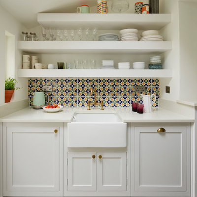 Transitional gray floor kitchen photo in London with a farmhouse sink, shaker cabinets, white cabinets, multicolored backsplash and white countertops
