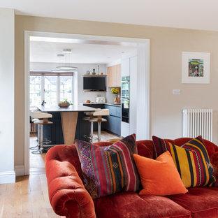 Offene, Mittelgroße Moderne Küche in U-Form mit Einbauwaschbecken, flächenbündigen Schrankfronten, Mineralwerkstoff-Arbeitsplatte, Rückwand aus Holz, schwarzen Elektrogeräten, Kücheninsel, beigem Boden und weißer Arbeitsplatte in Gloucestershire