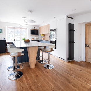 Inspiration for a medium sized modern u-shaped open plan kitchen in Gloucestershire with a built-in sink, flat-panel cabinets, composite countertops, wood splashback, black appliances, an island, beige floors and white worktops.