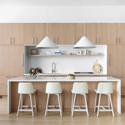 Large trendy u-shaped light wood floor and brown floor eat-in kitchen photo in New York with a drop-in sink, flat-panel cabinets, light wood cabinets, wood countertops, white backsplash, marble backsplash, stainless steel appliances, an island and white countertops