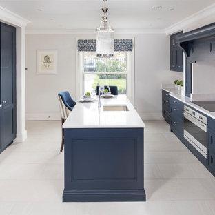 ダブリンのトランジショナルスタイルのおしゃれなキッチン (シェーカースタイル扉のキャビネット、青いキャビネット、珪岩カウンター、ミラータイルのキッチンパネル、シルバーの調理設備、アンダーカウンターシンク、白いキッチンパネル) の写真