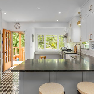 Inspiration for a mid-sized arts and crafts l-shaped eat-in kitchen in Vancouver with a farmhouse sink, shaker cabinets, grey cabinets, soapstone benchtops, white splashback, subway tile splashback, stainless steel appliances, marble floors, a peninsula, black floor and black benchtop.