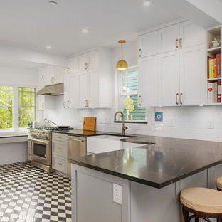 This is an example of a mid-sized arts and crafts l-shaped eat-in kitchen in Vancouver with a farmhouse sink, shaker cabinets, grey cabinets, soapstone benchtops, white splashback, subway tile splashback, stainless steel appliances, marble floors, a peninsula, black floor and black benchtop.