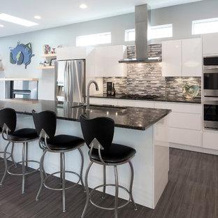 他の地域の中くらいのモダンスタイルのおしゃれなキッチン (フラットパネル扉のキャビネット、白いキャビネット、御影石カウンター、マルチカラーのキッチンパネル、シルバーの調理設備、アンダーカウンターシンク、石タイルのキッチンパネル、クッションフロア) の写真