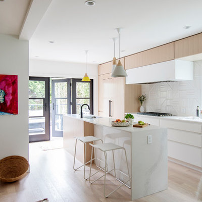 Kitchen - scandinavian galley light wood floor and beige floor kitchen idea in Vancouver with an undermount sink, flat-panel cabinets, white cabinets, white backsplash, paneled appliances, an island and quartz countertops