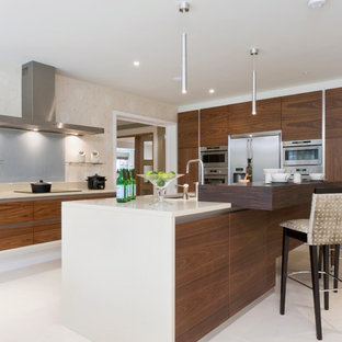 Inspiration for a medium sized contemporary kitchen in Buckinghamshire with flat-panel cabinets, grey splashback, glass sheet splashback, stainless steel appliances, an island, white floors, white worktops, a submerged sink and dark wood cabinets.