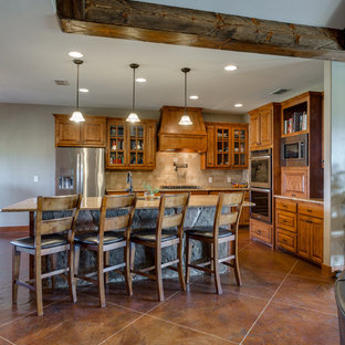 Example of a mid-sized mountain style l-shaped concrete floor and brown floor eat-in kitchen design in Austin with an undermount sink, raised-panel cabinets, medium tone wood cabinets, granite countertops, beige backsplash, travertine backsplash, stainless steel appliances and an island