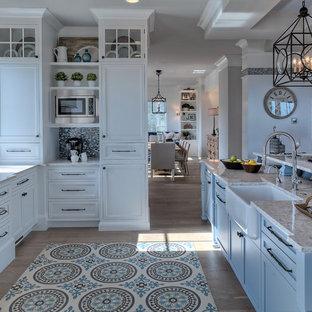 Foto på ett maritimt grå kök, med en rustik diskho, skåp i shakerstil, vita skåp, flerfärgad stänkskydd, stänkskydd i mosaik, rostfria vitvaror, mellanmörkt trägolv, en köksö och brunt golv