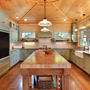 Photo of a country kitchen in Other with a farmhouse sink, green cabinets and panelled appliances.