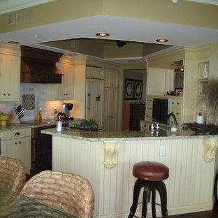 Idéer för ett mellanstort maritimt flerfärgad kök, med en rustik diskho, luckor med lamellpanel, gula skåp, granitbänkskiva, beige stänkskydd, stänkskydd i stenkakel, integrerade vitvaror, mörkt trägolv, en halv köksö och brunt golv