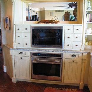 Maritim inredning av ett mellanstort flerfärgad flerfärgat kök, med en rustik diskho, luckor med lamellpanel, gula skåp, granitbänkskiva, beige stänkskydd, stänkskydd i stenkakel, integrerade vitvaror, mörkt trägolv, en halv köksö och brunt golv