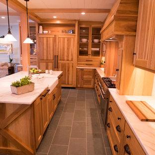 Cette image montre une cuisine chalet en U de taille moyenne avec un évier de ferme, un placard à porte shaker, des portes de placard en bois brun, un plan de travail en marbre, une crédence blanche, une crédence en marbre, un sol en ardoise et un sol vert.