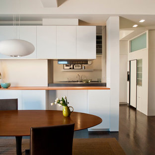 Design ideas for a contemporary eat-in kitchen in New York with flat-panel cabinets and orange benchtop.