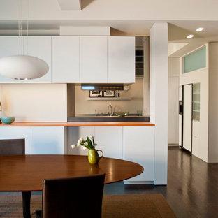 Idee per una cucina abitabile design con ante lisce e top arancione