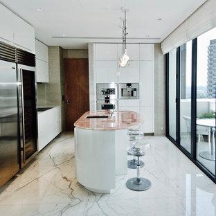 Modelo de cocina actual, de tamaño medio, con fregadero bajoencimera, armarios con paneles lisos, puertas de armario blancas, encimera de ónix, electrodomésticos de acero inoxidable, suelo de mármol, una isla, suelo blanco y encimeras rosas