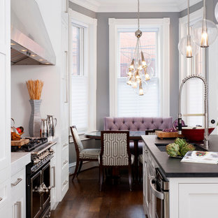 Design ideas for a large transitional galley eat-in kitchen in DC Metro with a single-bowl sink, shaker cabinets, white cabinets, soapstone benchtops, white splashback, stone slab splashback, black appliances, dark hardwood floors and with island.