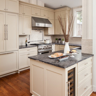 Mid-sized transitional u-shaped medium tone wood floor and brown floor open concept kitchen photo in DC Metro with a farmhouse sink, recessed-panel cabinets, beige cabinets, granite countertops, beige backsplash, ceramic backsplash, stainless steel appliances and a peninsula