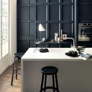 バンクーバーの大きいカントリー風おしゃれなキッチン (一体型シンク、落し込みパネル扉のキャビネット、青いキャビネット、人工大理石カウンター、シルバーの調理設備の、濃色無垢フローリング、茶色い床、白いキッチンカウンター) の写真