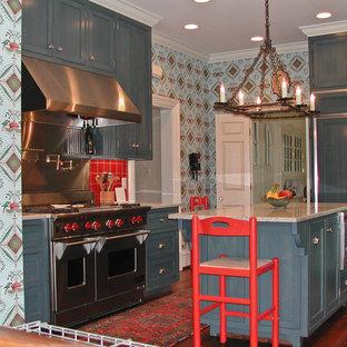 バーミングハムの中サイズのエクレクティックスタイルのおしゃれなキッチン (シェーカースタイル扉のキャビネット、青いキャビネット、テラゾーカウンター、赤いキッチンパネル、セラミックタイルのキッチンパネル、シルバーの調理設備、濃色無垢フローリング、茶色い床) の写真