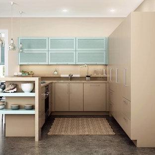 シンシナティの小さいコンテンポラリースタイルのおしゃれなキッチン (アンダーカウンターシンク、ルーバー扉のキャビネット、青いキャビネット、人工大理石カウンター、シルバーの調理設備の、コンクリートの床、茶色い床、ベージュのキッチンカウンター) の写真