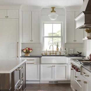 マイアミのカントリー風おしゃれなキッチン (エプロンフロントシンク、シェーカースタイル扉のキャビネット、白いキャビネット、白いキッチンパネル、濃色無垢フローリング、茶色い床、黒いキッチンカウンター) の写真