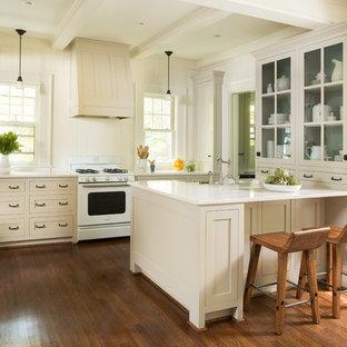 Klassische Küche mit beigen Schränken, Quarzwerkstein-Arbeitsplatte, Küchenrückwand in Weiß, weißen Elektrogeräten, braunem Holzboden, Halbinsel und Glasfronten in Atlanta