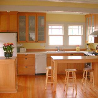Mittelgroße Klassische Wohnküche in U-Form mit Doppelwaschbecken, Schrankfronten im Shaker-Stil, hellen Holzschränken, Mineralwerkstoff-Arbeitsplatte, Küchenrückwand in Gelb, weißen Elektrogeräten, hellem Holzboden und Halbinsel in Seattle
