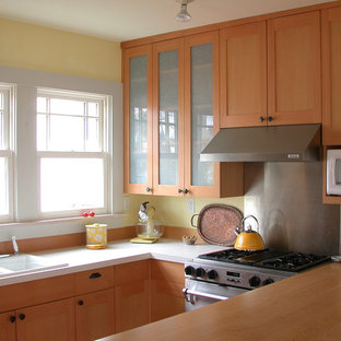 Inspiration for a mid-sized arts and crafts galley open plan kitchen in Seattle with a double-bowl sink, shaker cabinets, light wood cabinets, quartzite benchtops, yellow splashback, white appliances, light hardwood floors and a peninsula.