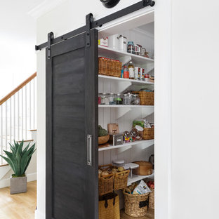 Mid-sized traditional kitchen pantry photos - Example of a mid-sized classic light wood floor kitchen pantry design in Boston with open cabinets, white cabinets, a farmhouse sink, marble countertops, stainless steel appliances and an island