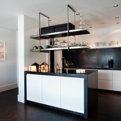 Inspiration for a modern l-shaped kitchen remodel in New York with flat-panel cabinets and black backsplash