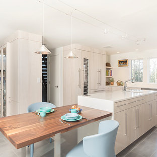 Mid-sized scandinavian eat-in kitchen ideas - Inspiration for a mid-sized scandinavian u-shaped porcelain floor eat-in kitchen remodel in New York with a farmhouse sink, flat-panel cabinets, light wood cabinets, quartz countertops, paneled appliances and an island