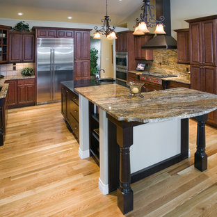 Large elegant u-shaped light wood floor eat-in kitchen photo in Denver with an undermount sink, raised-panel cabinets, dark wood cabinets, granite countertops, multicolored backsplash, stone slab backsplash, stainless steel appliances and an island
