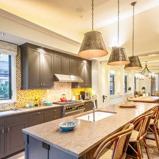 Foto di una cucina classica con lavello sottopiano, ante in stile shaker, ante marroni, paraspruzzi beige, paraspruzzi con piastrelle a mosaico, elettrodomestici in acciaio inossidabile e isola