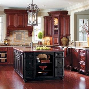 Foto di una grande cucina classica con ante con bugna sagomata, ante in legno bruno, top in quarzo composito, paraspruzzi in travertino, parquet scuro, pavimento rosso, lavello stile country e paraspruzzi multicolore
