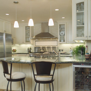 Traditional kitchen inspiration - Elegant u-shaped kitchen photo in San Francisco with glass-front cabinets, stainless steel appliances, granite countertops, an undermount sink, beige cabinets, beige backsplash and subway tile backsplash