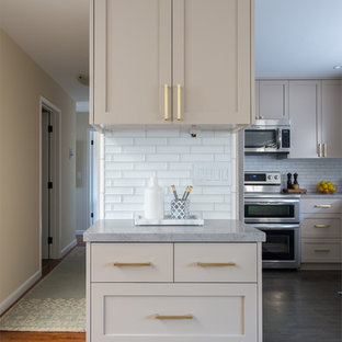 Inspiration for a mid-sized midcentury u-shaped kitchen in San Diego with an undermount sink, shaker cabinets, beige cabinets, quartz benchtops, white splashback, ceramic splashback, stainless steel appliances, limestone floors, with island and beige floor.