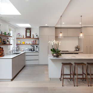This is an example of a medium sized contemporary l-shaped kitchen in London with a double-bowl sink, flat-panel cabinets, grey cabinets, marble worktops, light hardwood flooring, an island and grey floors.