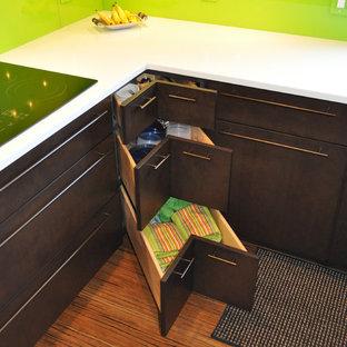 Modelo de cocina comedor en U, minimalista, con fregadero bajoencimera, armarios con paneles lisos, puertas de armario de madera en tonos medios, encimera de cuarzo compacto, salpicadero gris, salpicadero de vidrio templado, electrodomésticos negros, suelo de bambú y una isla