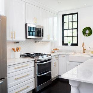 На фото: отдельные, параллельные кухни в стиле современная классика с белыми фасадами, столешницей из кварцита, белым фартуком, фартуком из плитки кабанчик, техникой из нержавеющей стали, деревянным полом, фасадами в стиле шейкер, раковиной в стиле кантри и черным полом